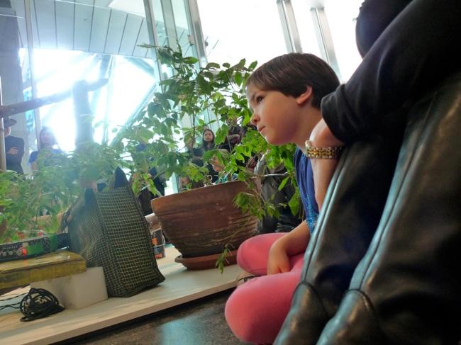 A kid checks out Dylan's drum robotics